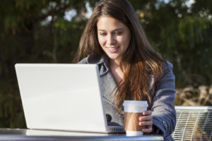young woman working on her laptop in an outdoor caafe