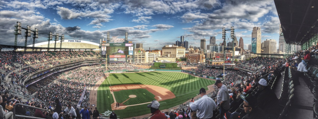 fish eye lens shot of baseball stadium with tens of thousands of fans all wearing sports merchandise