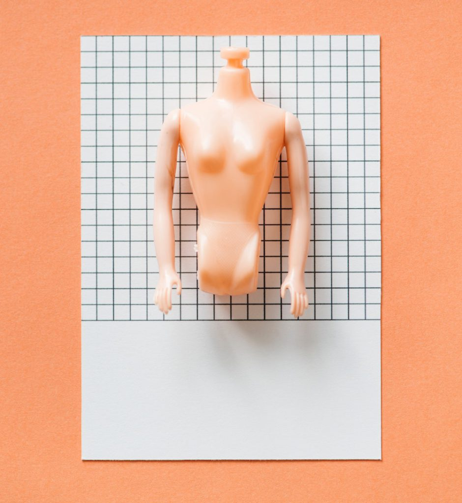 naked plastic barbie doll with no head or legs
