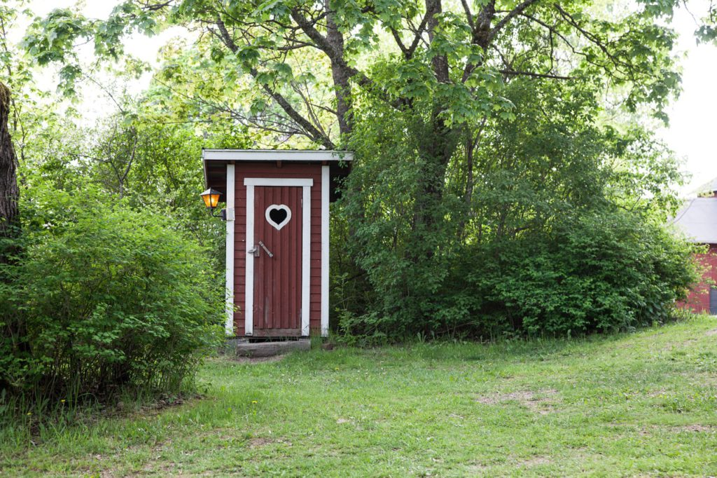 red and white outhouse with heart shaped hole in the door