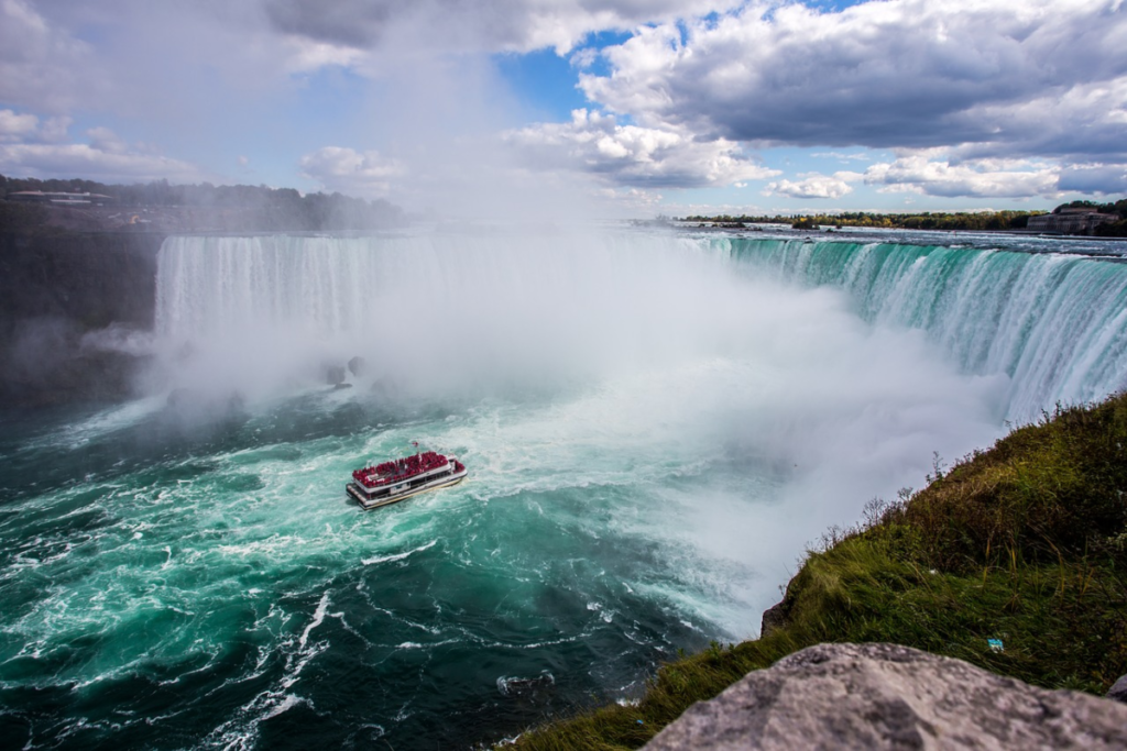 panoramic image of niagra falls with large tourist boat in the mist to represnent travel affiliate programs for Canada