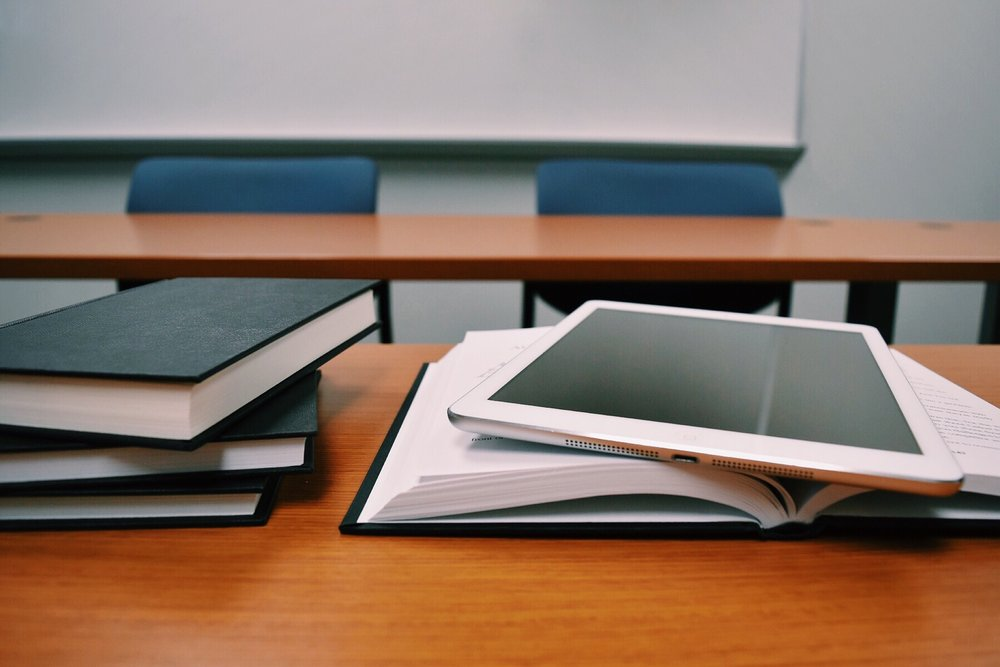 tablet, book, and desk to represent online education affiliate programs