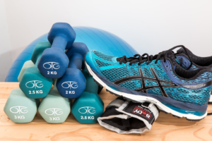 This photo shows fitness equipment including dumbbells, running shoes, an exercise ball stacked on a table.