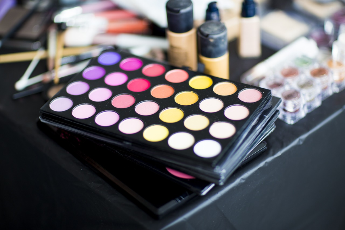 photo of a makeup tray with various colors and makeup brushes plus other beauty products around the makeup.