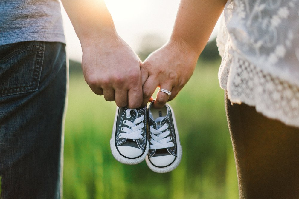 A couple holding baby shoes to represent family affiliate programs