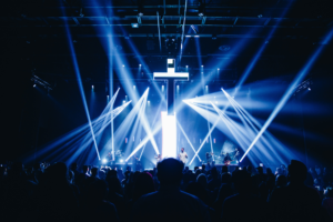 This is a photo of a cross/crucifix hanging above a stage at a Christian rock concert with stage lighting around it