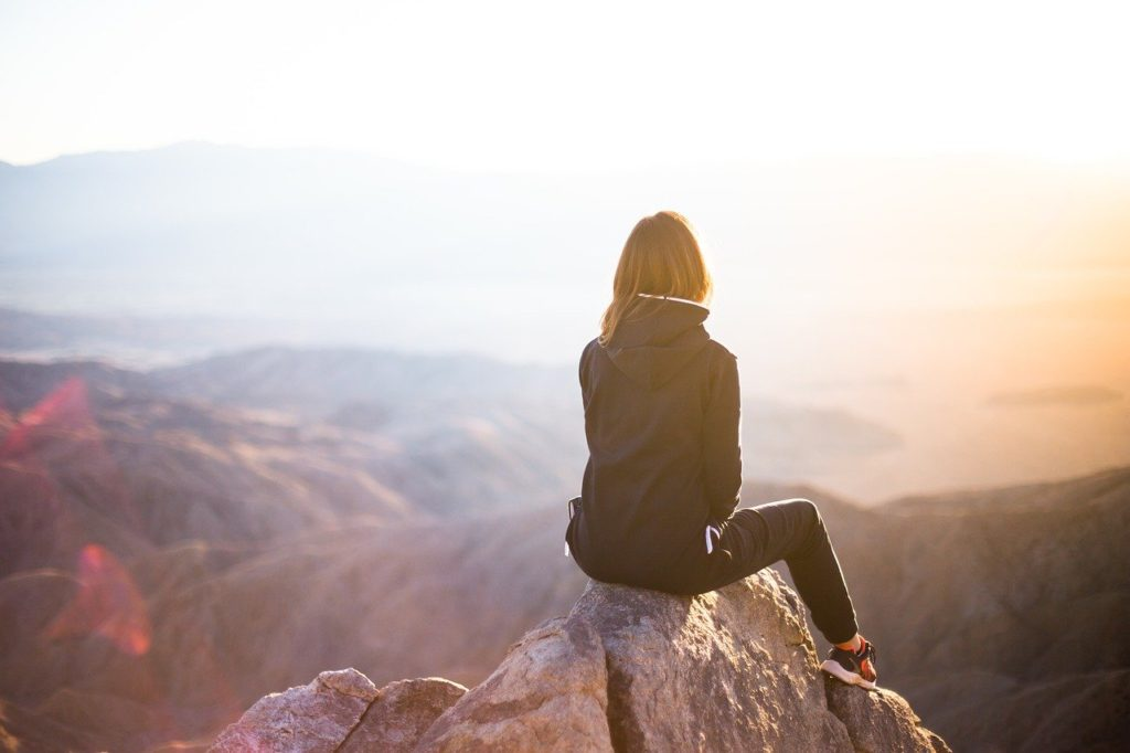 Woman sitting on a mountain top to represent travel affiliate programs