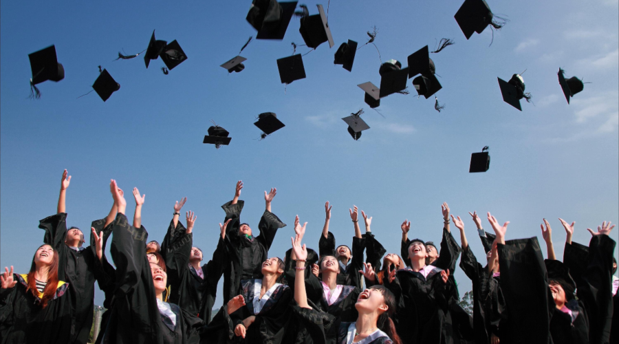 Picture shows a crowd of students wearing graduation gowns, throwing their hats in the air in celebration of graduating from higher education.