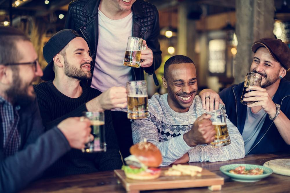 group of diverse men having beers and burgers to represent the best men's affiliate programs