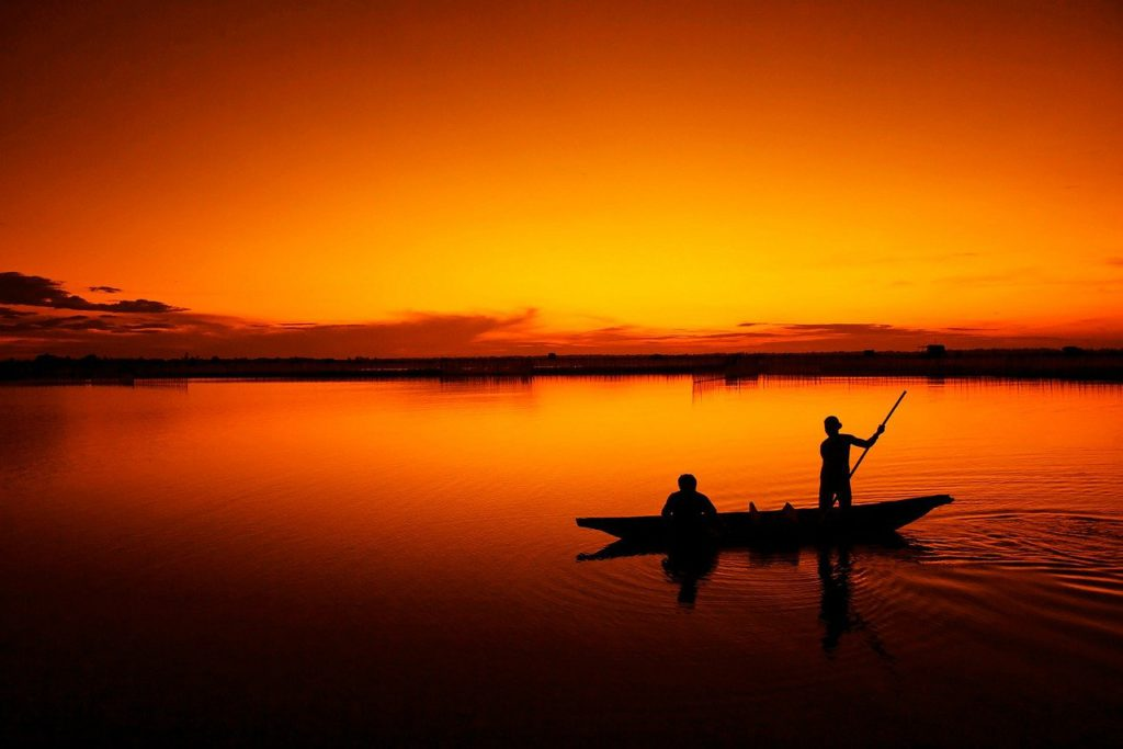 the silhouette of two people fishing from a boat to represent fishing affiliate programs