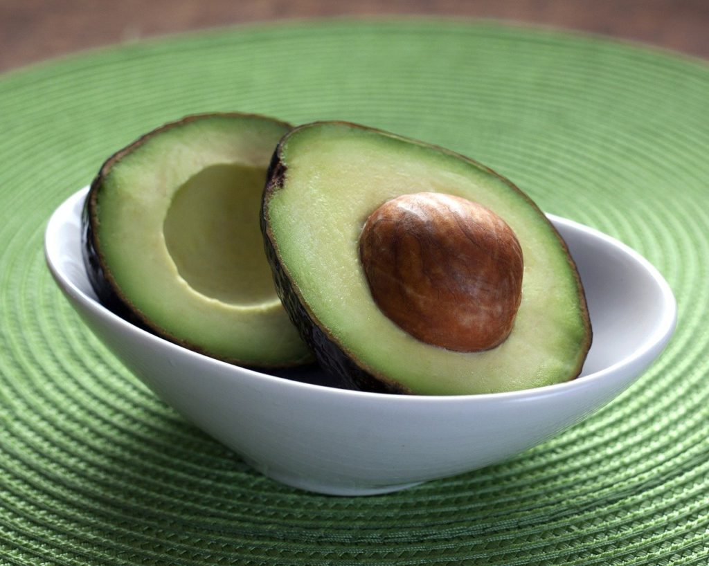 an avocado cut in half in a bowl to represent ketogenic affiliate programs