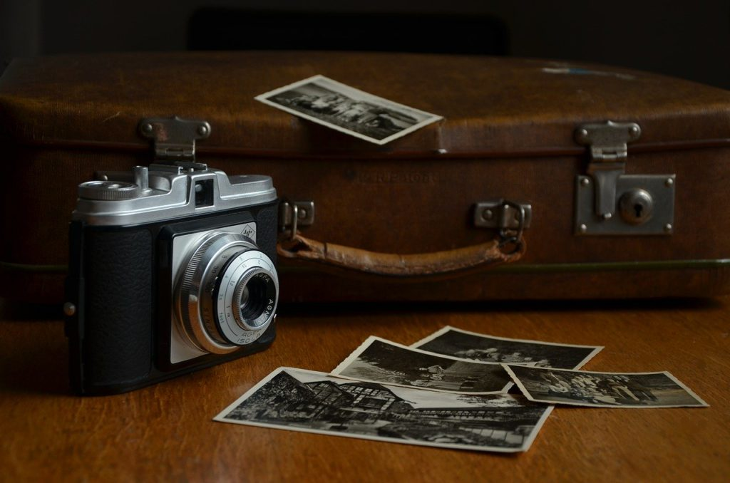 a camera and photos on a table to represent photography affiliate programs