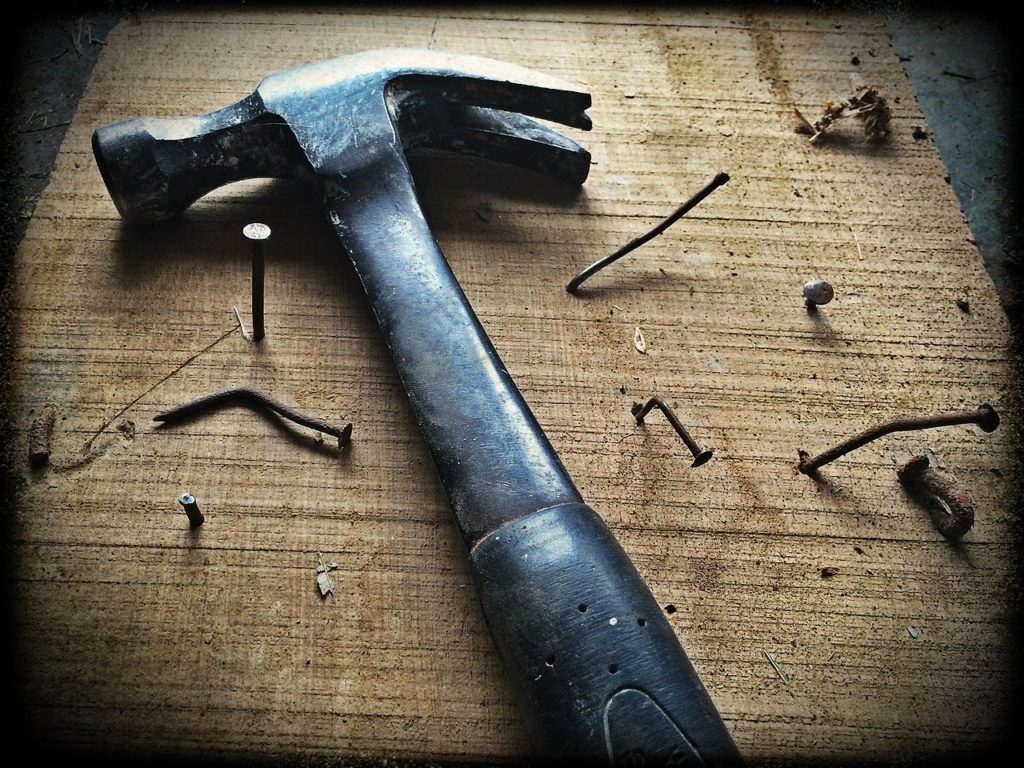 a hammer and nails in a board to represent woodworking affiliate programs