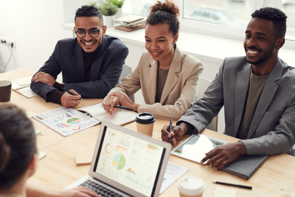 The image represents a startup founder pitching a business plan to a small panel of three investors using a slideshow on a laptop with the same same graphs, charts and similar graphics in print to present to each panelist.