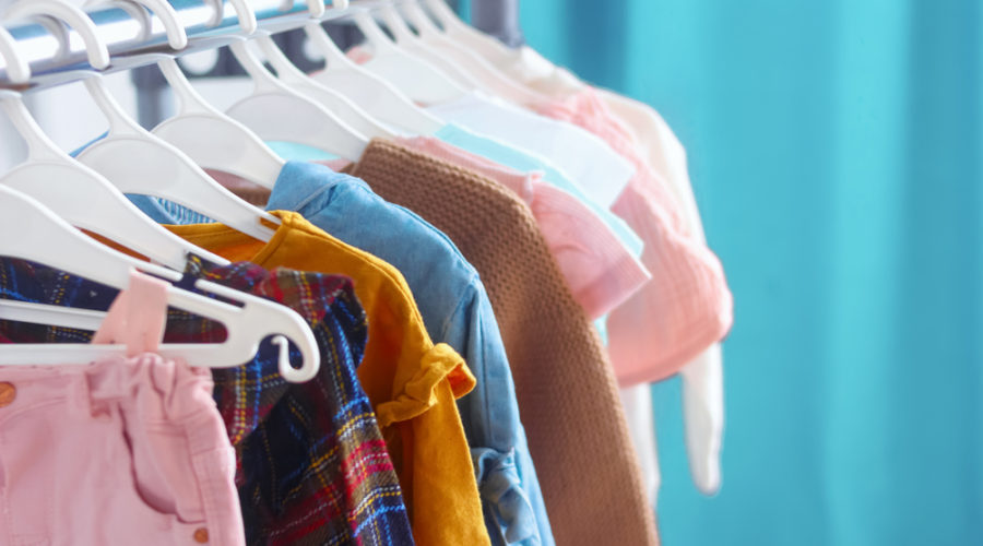 A selection of children's clothing in pastal colors hanging from coat hangers against a blue background