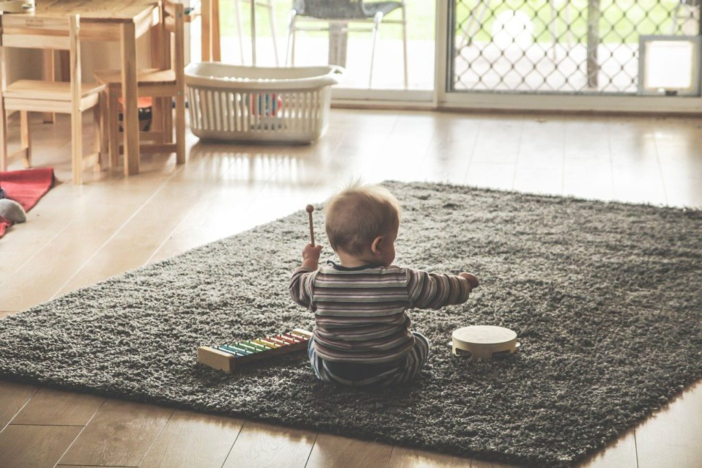 a baby playing with toys on a carpet to represent baby product affiliate programs