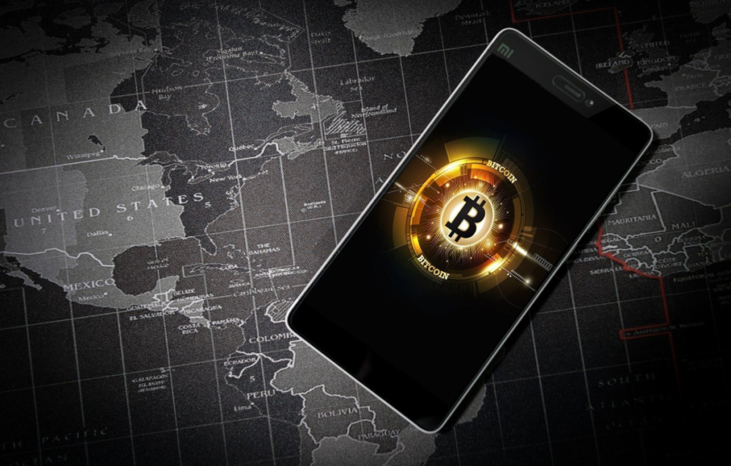 Bitcoin was the first cryptocurrency to be accepted globally and remains the dominant virtual currency around the world. This is reflected in this image showing a smartphone against the backdrop of a worldwide map. Bitcoin affiliate programs operate globally in support of borderless transactions.