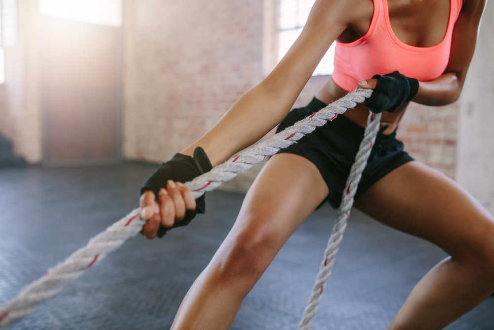 A close up image of a young woman in gym gear pulling on a rope