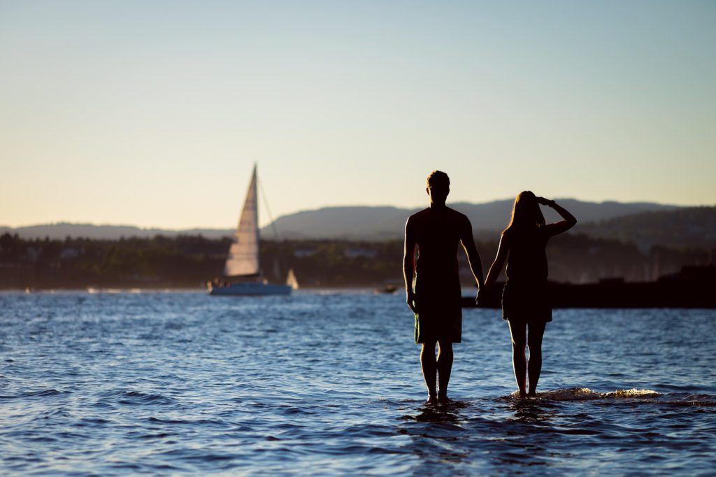 a couple holding hands while wading in some water to represent dating affiliate programs