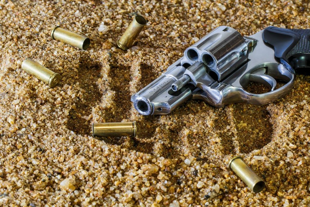 A gun and some bullets in the sand to represent gun affiliate programs