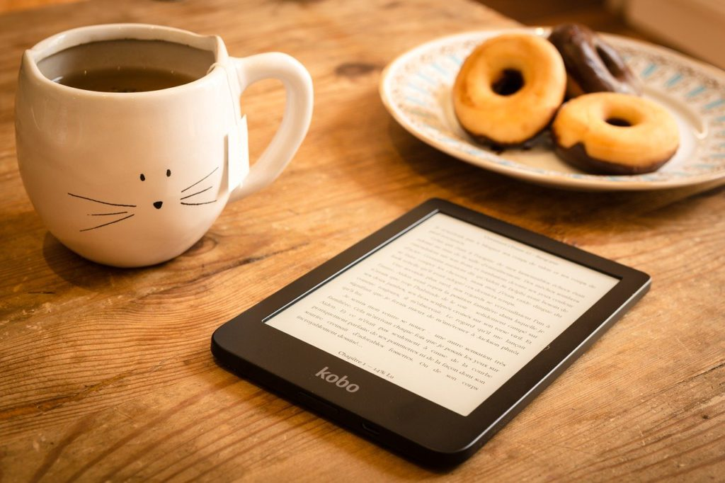 an ereader, coffee, and donuts on a desk to represent ebook affiliate programs