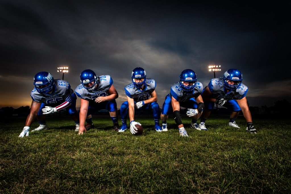 a row of football players lined up on the field to represent fantasy sports affiliate programs