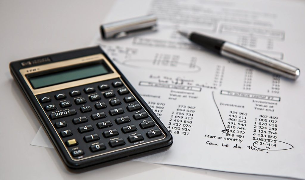 a pen, calculator, and budget sheet on a table to represent investing affiliate programs