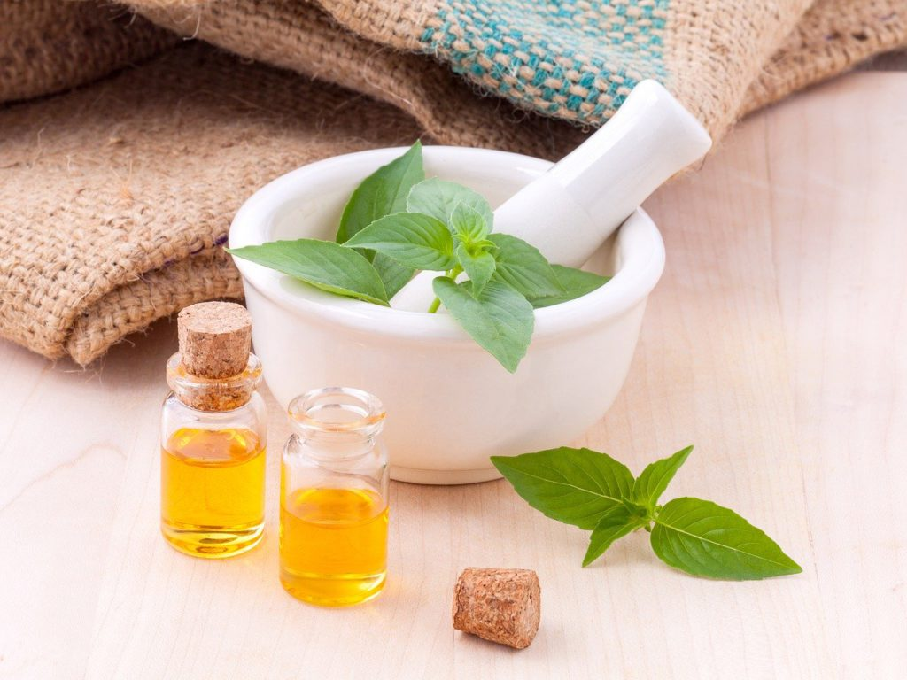 herbs and oil in a mixing bowl to represent natural remedies affiliate programs