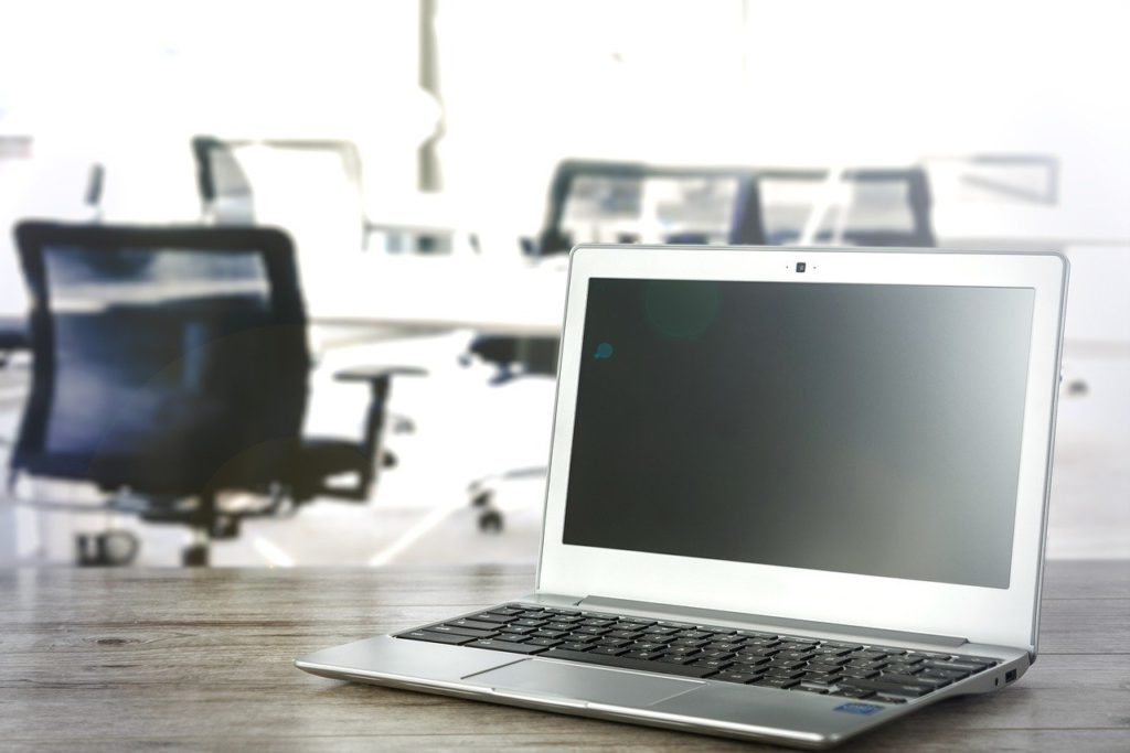a laptop on an office desk with chairs in the background to represent saas affiliate programs