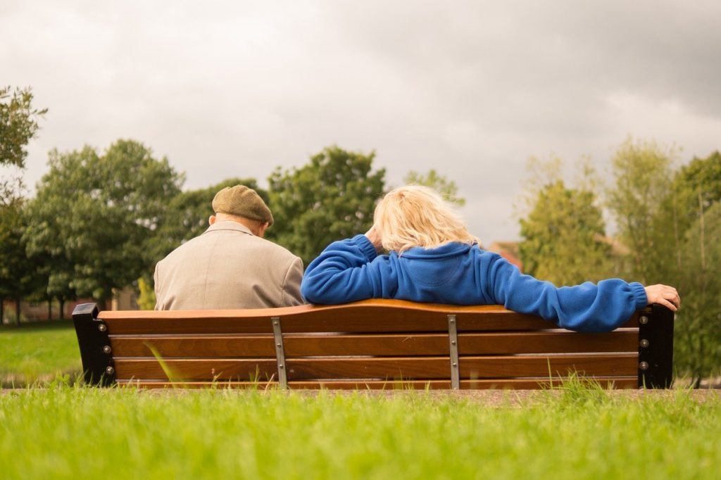 An older couple sitting on a bench in a park to represent senior living affiliate programs