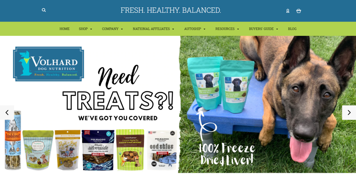 This is a screenshot taken from the home page of VolhardDogNutrition.com showing a photo of a German Shepherd alongside sachets of freeze dried liver dog treats.