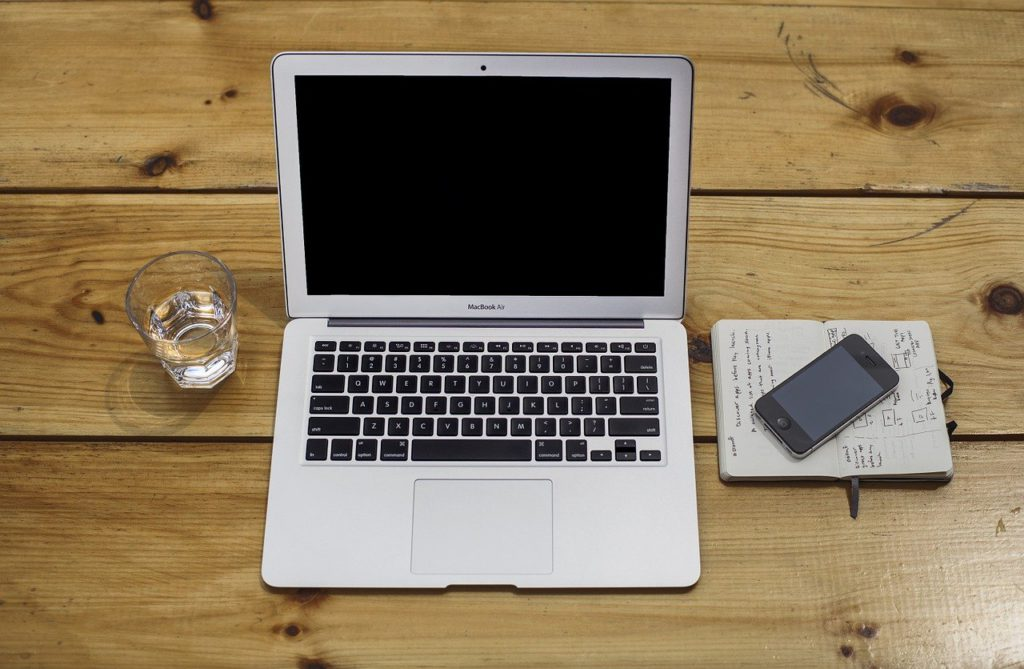 a laptop, cell phone, and notebook on a desk to represent software affiliate programs