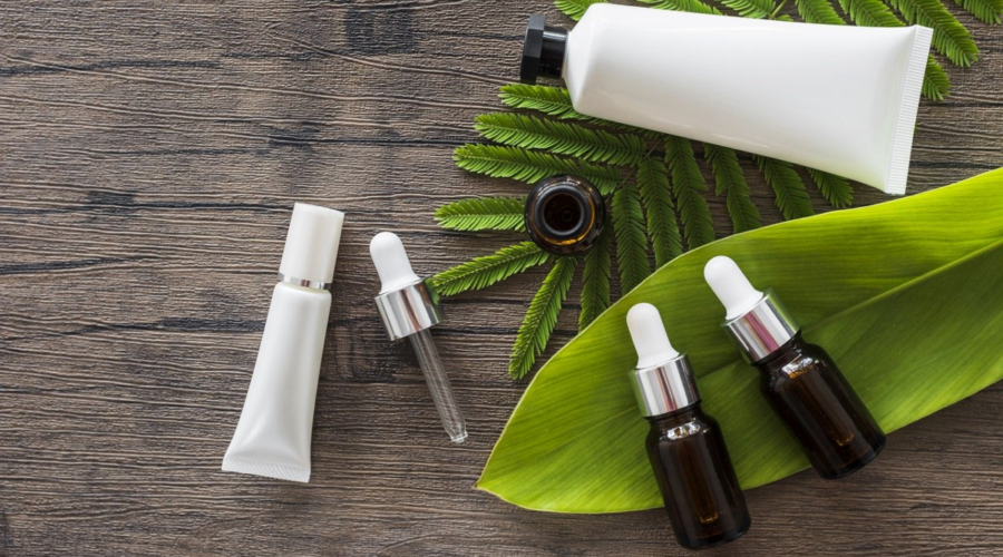 The image shows some plant leaves on a natural wood backdrop wtih a dispensing syringe and four plain (unbranded) bottles of different sizes and shapes suited to various aromatherapy products such as creams, lotions, carrier oils, and essential oils.