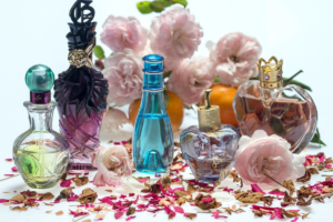 The image shows a variety of perfume decanters displayed with florals and petals representing some of the natural ingredients used in perfumes.