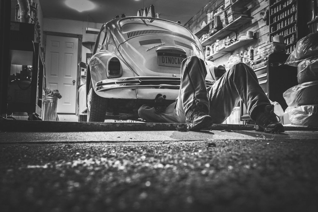 a man underneath a car making repairs to represent car and auto parts affiliate programs