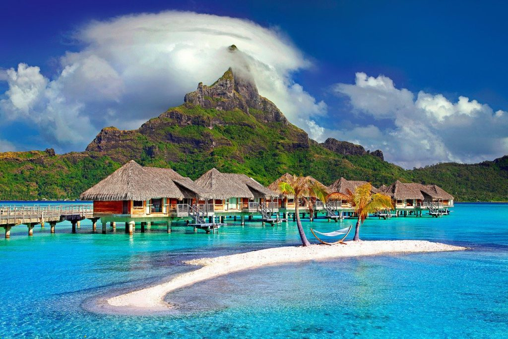 several villas on the beach with a mountain in the background to represent luxury travel affiliate programs