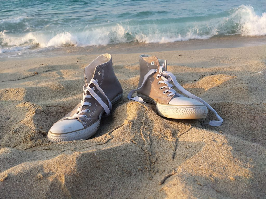 a pair of sneakers on the beach to represent sneakers affiliate programs