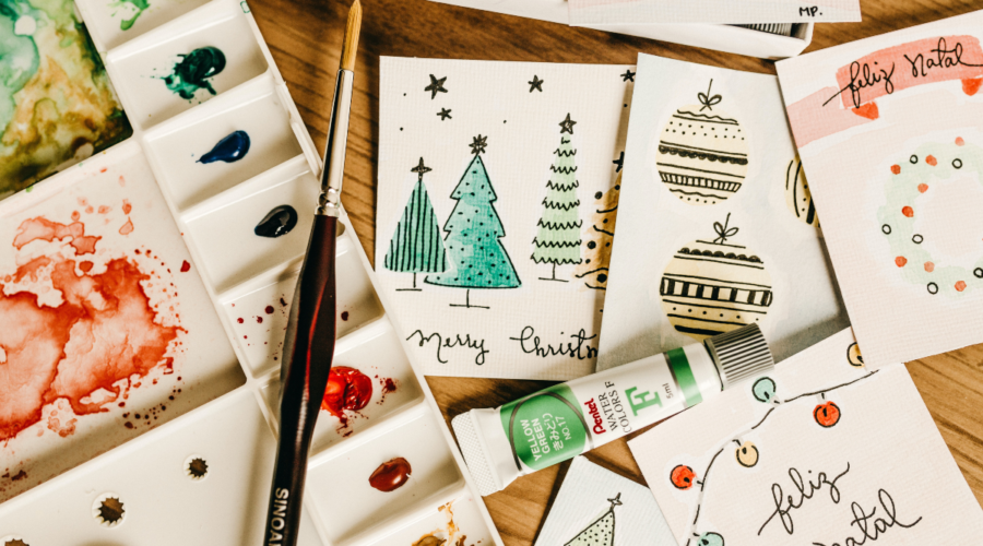 The image shows a few seasonal greeting cards being created by an artist using paints to create their own designs.