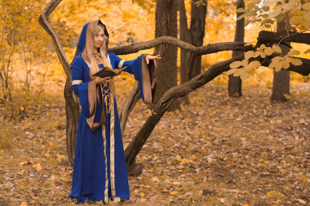 This image shows a young woman dressed in a long Royal blue hooded cloak standing in a forest holding a Book of Shadows which is used for rituals and spell casting. Witchcraft affiliate programs can be used to earn from sales of all witchcraft apparel shown in the picture.