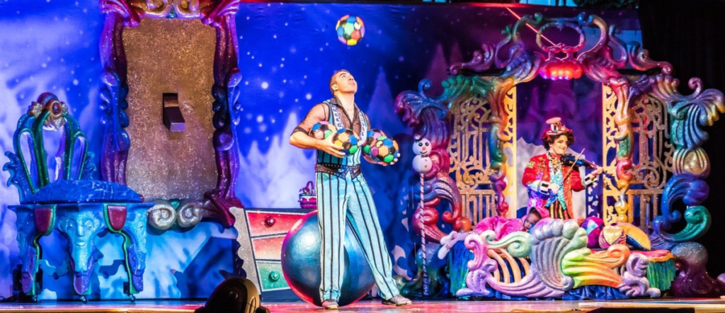 The image shows a stage performance featuring professioanl backdrops, a juggler and a musician, representing just three sectors (art, talent, live music) within the larger live entertainment industry.