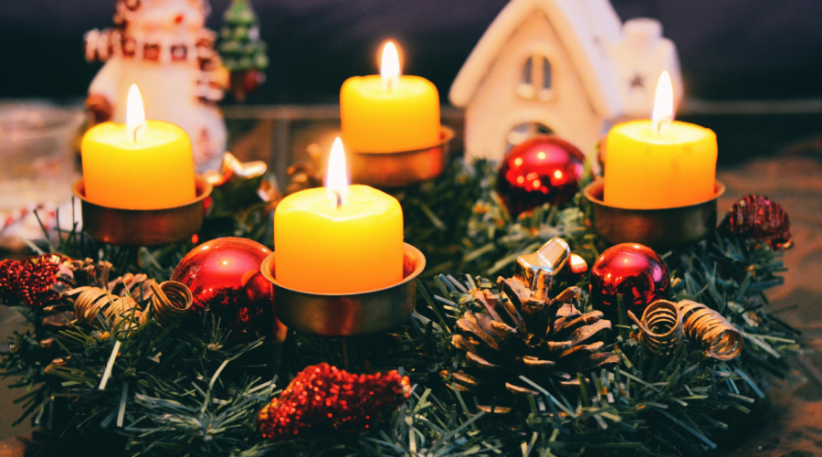 The image shows four lit yellow candles in a decorative wreath used as part of a festive table display.
