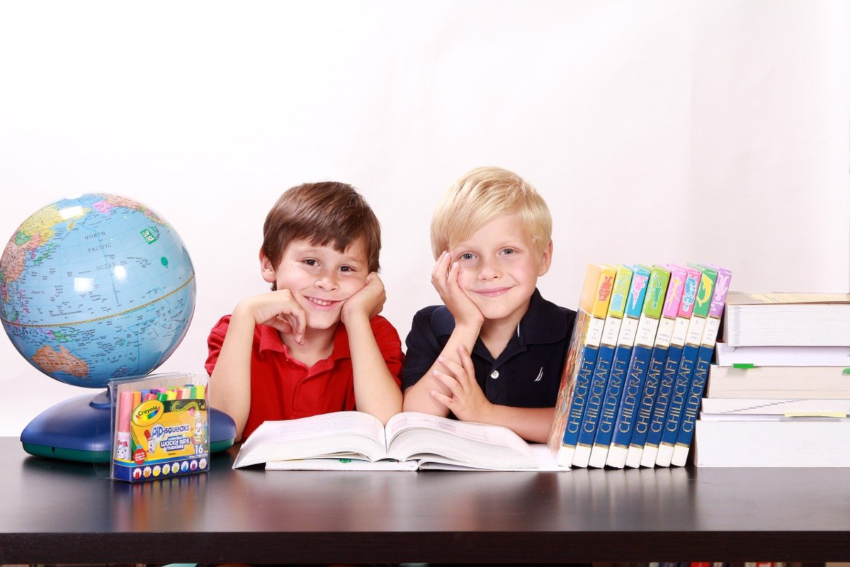 This is a photo showing two boys studying together with some education material in front of them including a textbook, world globe, coloring pens and a book collection stacked on the table.